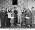 Smiling man has chest measured in front of group holding chest x-ray signs, Pierce County, ca. 1957