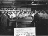 Class of the first Apprenticeship Meatcutting School behind table with sides of meat, 1946