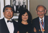 Gordon Hirabayashi, Fred Korematsu wearing a medal and a woman in front of a photograph, May 17,...