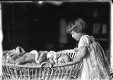 Child and baby in baby carriage (possibly Loyal with older sister Carol), n.d.