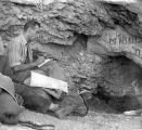 Man writing in notepad in front of rock outcrop, Serbia,  August 28, 1950