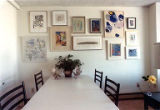 Dining room table in front of wall covered in artwork, probably Theodosia Young Young's home, ...