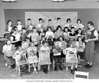 Elementary school students posing with health posters and booklets in classroom, Pierce County...