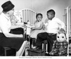 Older woman talking to two African-American children, Pierce County Tuberculosis League program,...