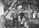 Family group with two children sitting in yard of homestead, 1909-1910