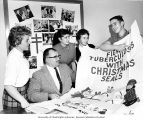 Jim Smith holding up Christmas Seals poster while Madeline Shouse, John Krilich, Roberta Reed,...