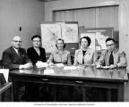 Doctors and officials sit at table in front of tuberculosis case maps of Tacoma, Pierce County...