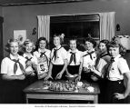 Campfire girls pose in front of table with ornaments made of pine cones and Christmas Seals,...