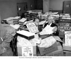 Two men surrounded by carts and boxes full of Christmas Seals envelopes during Christmas Seals...