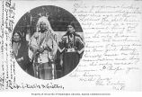 Native American known as Lap-i-tash wearing a headress standing next to his sister and...