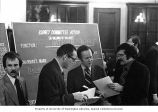 Representative Brock Adams with unidentified men at a Budget Committee meeting in Washington, D....