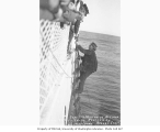 Captain McMullen of the steamer EDITH boarding the MARIPOSA after rescue, off LaTouche Island, 1915