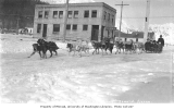 Dogsled team pulling sled full of people down city street, Seward, ca. 1912