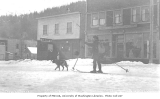 Man on skis being pulled down street by a dog, Seward, ca. 1912