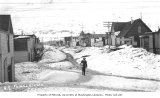 Man walking along snow-covered streets of Valdez, ca. 1912