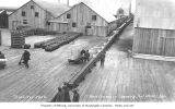 Conveyer belt, workers and buildings at Pacific American Fisheries cannery at Port Moller, ca. 1912
