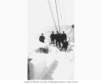 Crew on bow of ice-covered steamer DORA, April 13, 1910