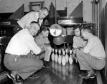 Five men crowded around bowling pins in bowling alley, Lake Washington Shipyard, Houghton,...