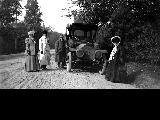 Men and women with automobile on dirt road, ca. 1909
