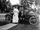 Man and woman with automobile, ca. 1908