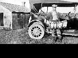 Man in front of automobile with catch of fish, n.d.