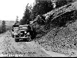 Work crew and vehicles on side of road, April 12, 1937