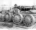 Worker with guide rolls for the draw pontoon, Lake Washington Floating Bridge construction,...
