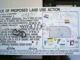 Notice of Proposed Land Use Action sign with graffiti tags
