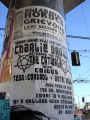 Event poster on pole featuring three musical groups