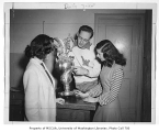 Bill Joost showing crew trophy to two students, University of Washington, January 1947