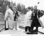 University of Washington crew officials standing on a boat during a competition, probably on Lake...