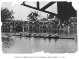 Crew rowing under bridge with spectators on shore, University of Washington, 1925