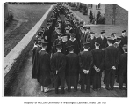 Edmond Meany and other faculty walking between rows of graduates, University of Washington, ca....