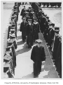 Edmond Meany and other faculty walking between rows of graduates, University of Washington, June...