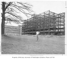 Man playing golf in front of construction of the University Teaching Hospital adjacent to the...