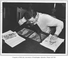 Forestry student studying maps and photographs, University of Washington, ca. 1940
