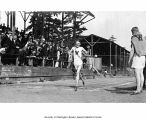 Runner crossing the finish line while crowd looks on during a track and field event, University of...