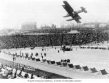 Game of pushball being played at the stadium during military event showing bi-plane flying...