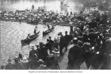 Crowd watching students engaged in mock battle from canoes as part of Junior Day, University of...
