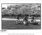 Students on lawn near blooming cherry trees, University of Washington, March 1982