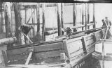 Men working on a large trap next to a dock, University of Washington's Marine Station at Friday...