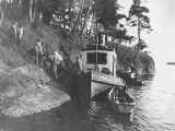 Men unloading luggage from the boat VIOLET on rocky shore, University of Washington's Marine...
