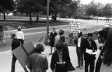Man holding sign and standing on sidewalk during philosophy teaching assistant picket line in...