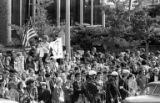 Protesters waving flags and holding signs in front of Central Library during the Vietnam...