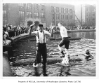 Students in log-rolling contest in Frosh Pond on Garb Day, University of Washington, 1964