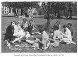 1929 Campus Day showing students eating lunch on grass, University of Washington