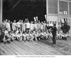 University of Washington crew receiving pep talk from a coach in front of the shellhouse, Seattle,...