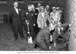 Dr. Henry Schmitz and W.R. Hill plant a sprig of ivy uisng the ceremonial spade as others look on,...