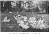 1930 Campus Day showing students eating lunch on grass, University of Washington