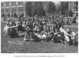 1933 Campus Day showing students sitting on grass, University of Washington